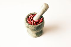 Red Capsules And Orange Pills With Mortar Pestles On White Background. Stock Photos