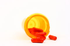 Red Capsules Spilling Out Of A Bottle Health Care Concept. Red medication capsules spilling from the prescription bottle onto a light colored background Stock Images