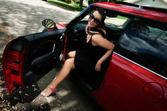 Red car. Woman getting out of the car Royalty Free Stock Photos
