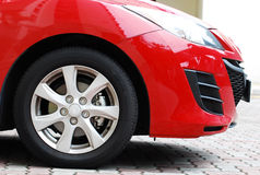 Red Car. The front side view of a car showing one wheel and headlight Royalty Free Stock Image