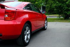 Red car. Red sports car in the parking lot. Rear view from the side stock photography