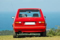 Red car. Back view of a small red car (VW City Golf Shuttle) standing and parked on the lawn outdoors in front of blue sky Royalty Free Stock Photography
