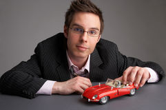 Red car. Businessman with a red miniature car Stock Photography