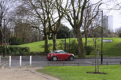 Red car against London park. Red fancy car against London green park royalty free stock photos