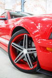 Red car with alloy wheel indoor.  Royalty Free Stock Photography