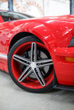 Red car with alloy wheel indoor.  Stock Photo
