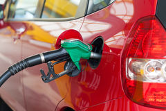 Red car being filled with fuel Stock Photos