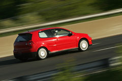 Red Car Blur. Red car speeding down highway in late afternoon sun royalty free stock photography