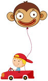 A red car with a boy and a monkey balloon Stock Photography