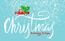Red car carries Christmas spruce. Christmas is coming to town. Christmas Lettering. Royalty Free Stock Photo