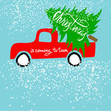 Red car carries Christmas spruce. Christmas is coming to town. Christmas Lettering. Royalty Free Stock Image