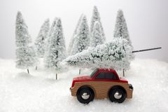 Car carrying a Christmas tree in a snow covered miniature evergreen forest. Red car carrying a Christmas tree in a snow covered miniature evergreen forest Stock Photos