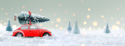 Red Car Carrying A Christmas Tree. In The Snowy Forest