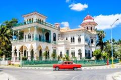 Palacio de Valle, Cienfuegos, Cuba. Red car in Cienfuegos street in front of Palacio de Valle, Cuba Stock Photo