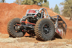 Red Car climbing out steep dugout, front tires gripping on flat. Rustenburg, South Africa – JUNE 17, 2017: National Extreme Modified 4x4 Vehicle Championship Royalty Free Stock Photo