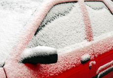 Red car covered with snow, close-up. Royalty Free Stock Image