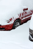 Red car covered with snow in winter blizzard Royalty Free Stock Photos