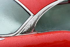 Red car detail. Detail of classic car with waterdrops Stock Photo