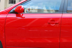 Red Car Door. A photo taken on the red paint side doors of a car royalty free stock image
