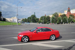 Red car drives along the Moscow Kremlin. Stock Photos