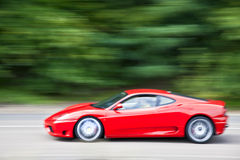 Red car driving fast on country road Royalty Free Stock Photo