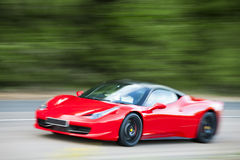 Red car driving fast on country road Royalty Free Stock Images