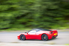 Red car driving fast on country road Royalty Free Stock Image