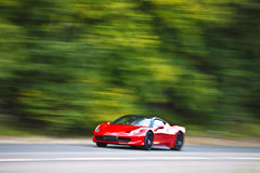 Red car driving fast on country road Stock Images