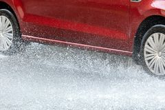 Red car driving through rain puddles creating splashes. Closeup Stock Photos