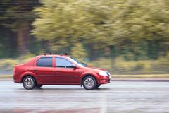 Red car is driving on a wet road. Sunny day after the rain Royalty Free Stock Image