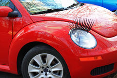 Red Car. Cute red car with eyelashes for girls or women, concept for feminine, fashion, or car accessories royalty free stock photos