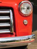 Red Car Front. Front of an old red car with headlight, blinker and chromed radiator grill and bumper Stock Photo