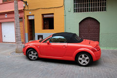 Red car in front of beautiful buildings in a street in Puerto de la Cruz in Tenerife Canary Islands, Spain, Europe. Red car in front of beautiful colorful Royalty Free Stock Photography