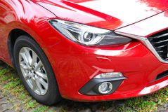 Red car front side view showing the right headlights and wheel. A red car front side view showing the right headlights and right wheel Royalty Free Stock Image