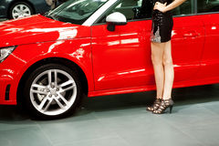 Red car and girl. Girl  posing near car at the motor show Stock Photo