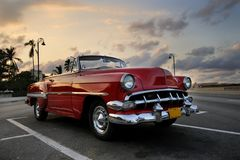 Red car in Havana sunset. View of red classic vintage american car parked in havana street against sunset sky stock photos