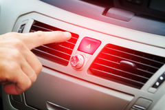 Red car hazard warning button. Driver pressing red triangle car hazard warning button stock photo