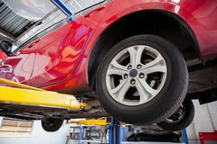 Vehicle lifted on hydraulic car lift. Red car lifted on hydraulic car lift in a workshop during routine service royalty free stock photography