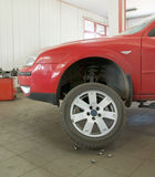 Red car lifted on raiser. Replacing winter tyre for summer tyre at the end of winter season in vulcanization works stock photography