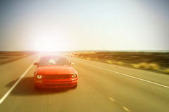 Red car in motion. Car In Motion Driving Fast, Speed Blur Royalty Free Stock Photography