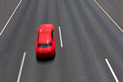 Red car moves fast on highway. Stock Image