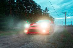 Red car moves over rough terrain with headlights Royalty Free Stock Image