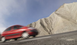 Red car in moving in a arid landscape Stock Image