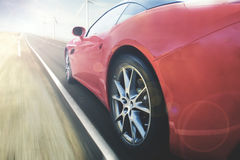 Red car is moving fast on the road. Back view of a luxury red car is moving fast on the asphalt road with the blur motion royalty free stock photography