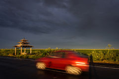 Red car moving on road with storm clouds in background Stock Photo