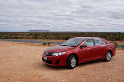 Red Car and Mt Connor in Outback Australia Stock Photos
