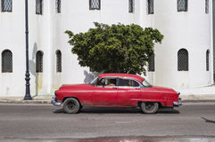 Red car in Old Havana, Cuba. American classic car running in front of the Ortodox Church in Old Havana, Cuba Royalty Free Stock Images