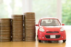 A red car over a lot of stacked coins Royalty Free Stock Images