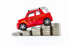 Red car over a lot of stacked coins. Royalty Free Stock Image