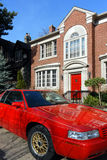 Red car parked in front of house stock photography